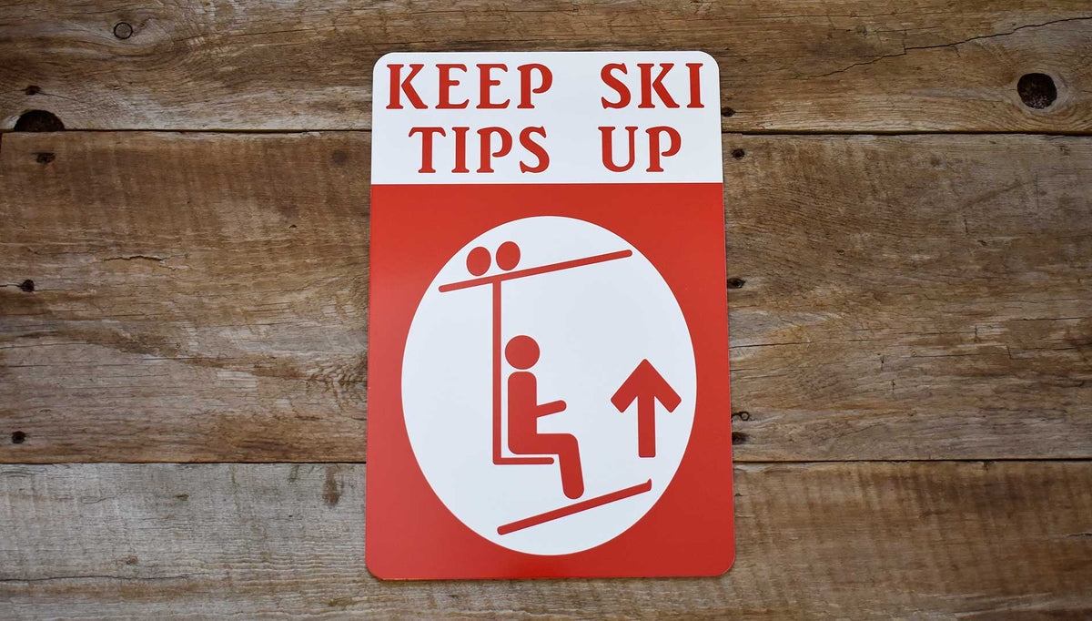 a metal sign with a white background and red text that says 'Keep Ski Tips Up' with an image of a skier on a chairlift