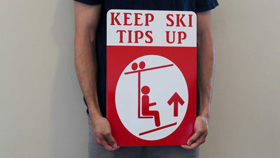 man holding a metal sign with a white background and red text that says 'Keep Ski Tips Up' with an image of a skier on a chairlift