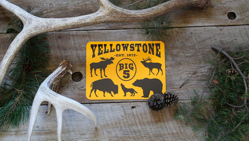 metal sign with a yellow background and black text that says 'Yellowstone Big 5' with black outlines of a moose, elk, bison, wolf, and grizzly bear with antlers and pine needles and cones around it
