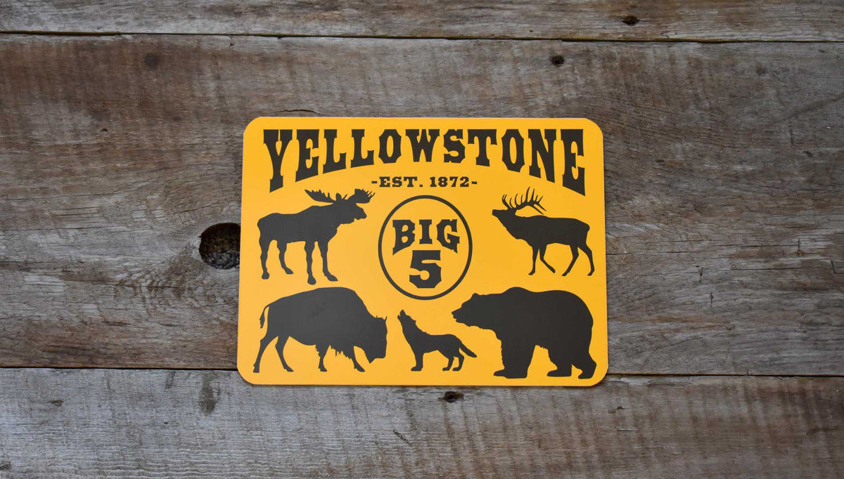 metal sign with a yellow background and black text that says 'Yellowstone Big 5' with black outlines of a moose, elk, bison, wolf, and grizzly bear
