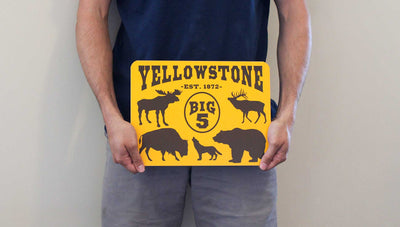 man holding a metal sign with a yellow background and black text that says 'Yellowstone Big 5' with black outlines of a moose, elk, bison, wolf, and grizzly bear