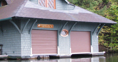 custom metal lake cabin sign that is brown and white hung up on a boat storage building
