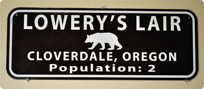 metal sign with white text that says 'lowery's lair' on a brown background