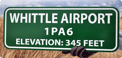 metal sign with white text that says 'whittle airport' with a green background