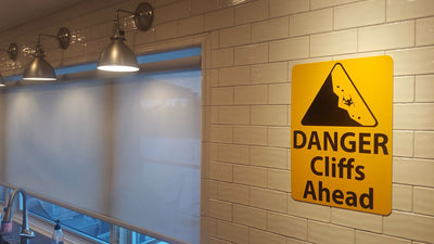 metal sign with black text saying 'danger cliffs ahead' with a yellow background and image of falling rock hung up on a wall