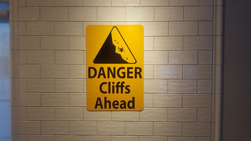 metal sign with black text saying 'danger cliffs ahead' with a yellow background and image of falling rock