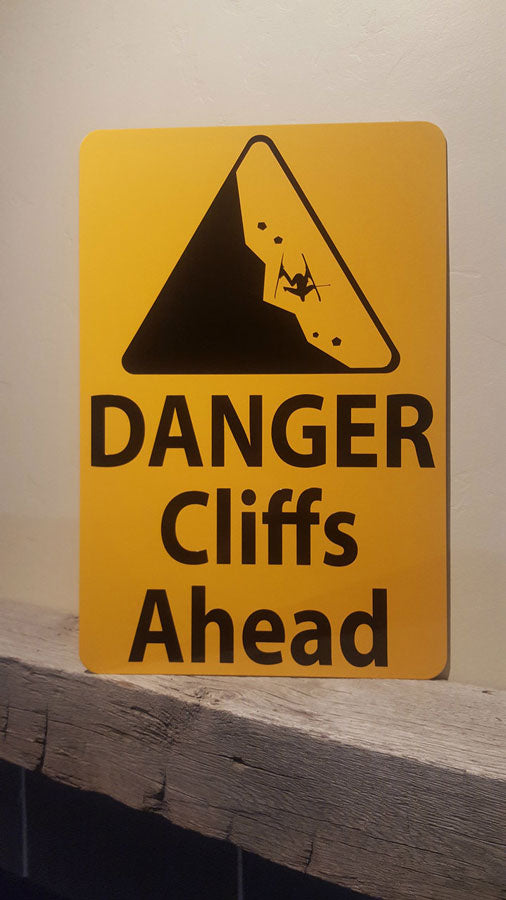 close up picture of metal sign with black text saying 'danger cliffs ahead' with a yellow background and image of falling rock
