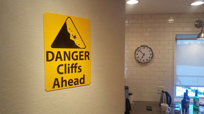 angled photo of a metal sign with black text saying 'danger cliffs ahead' with a yellow background and image of falling rock