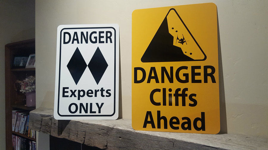 metal sign with black text saying 'danger cliffs ahead' with a yellow background and image of falling rock on a mantle