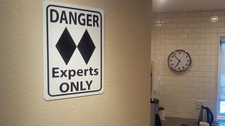 metal sign with black text saying 'danger experts only' with a two black diamonds on a white background