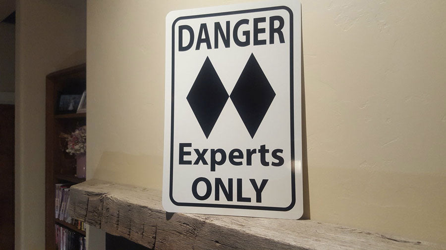angled photo of a metal sign with black text saying 'danger experts only' with a two black diamonds on a white background