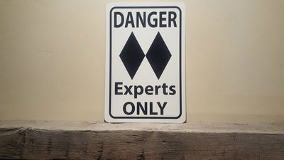 metal sign with black text saying 'danger experts only' with a two black diamonds on a white background on a mantle