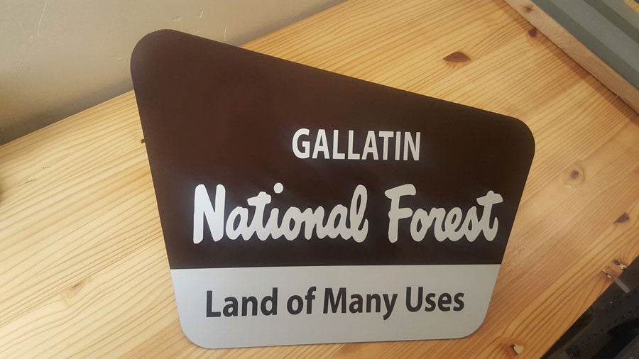 brown and white metal sign with text saying 'gallatin national forest land of many uses' on a wooden background