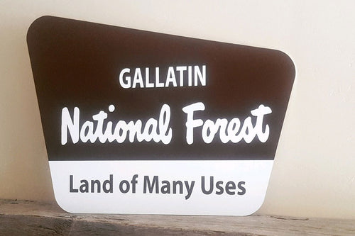 brown and white metal sign with text saying 'gallatin national forest land of many uses'