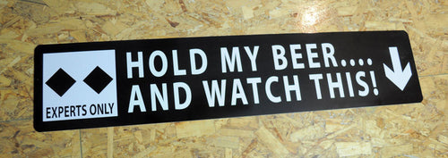 metal sign with white text saying 'hold my beer...and watch this!' with a black background and two black diamonds