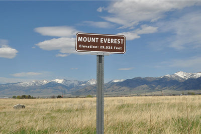 metal sign with a brown background and white text that says 'Mount Everest Elevation: 29,035 feet'