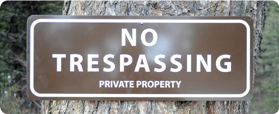 metal sign with white text saying 'no trespassing private property' with a brown background hung up on a tree