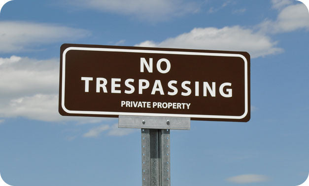 metal sign with white text saying 'no trespassing private property' with a brown background