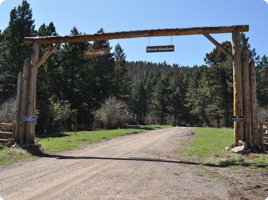 metal sign with white text saying 'no trespassing private property' with a brown background on a ranch entryway