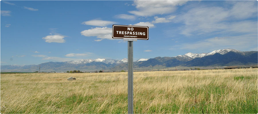 metal sign with white text saying 'no trespassing private property' with a brown background on a post