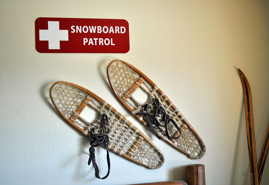 a metal snowboard patrol sign with a red background and white text that reads 'Snowboard Patrol' hung up on a wall