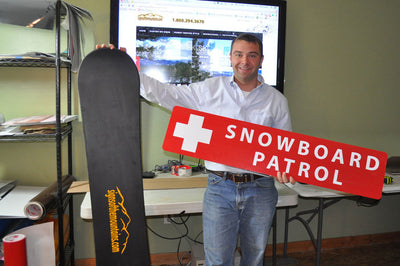 a man holding a metal snowboard patrol sign with a red background and white text that reads 'Snowboard Patrol' in one hand and a snowboard in the other hand