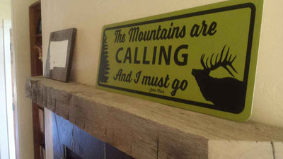 metal sign with a yellow background and black text saying 'the mountains are calling and i must go' on a mantle