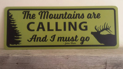 metal sign with a yellow background and black text saying 'the mountains are calling and i must go' with a black elk and tree outline
