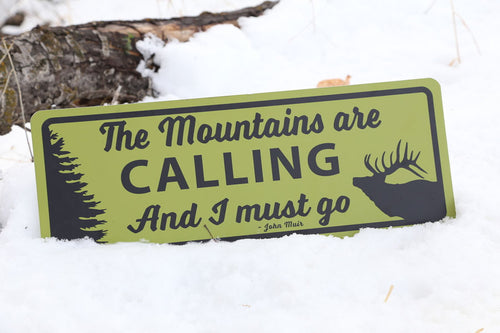 metal sign with a yellow background and black text saying 'the mountains are calling and i must go' in the snow