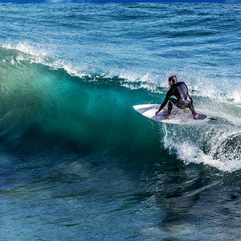 surfer with board on barrel wave