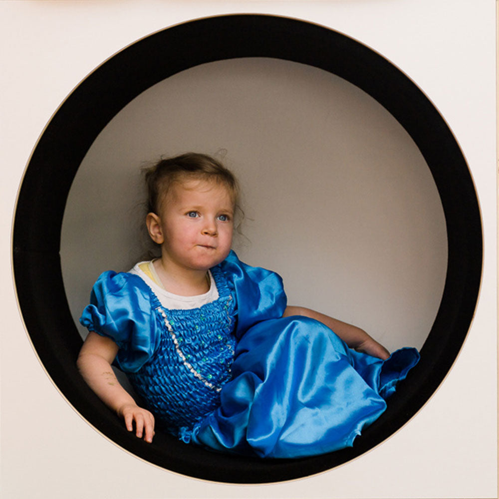 Little girl in a blue dress sitting in a round cubby hole at Spotted Frog Preschool