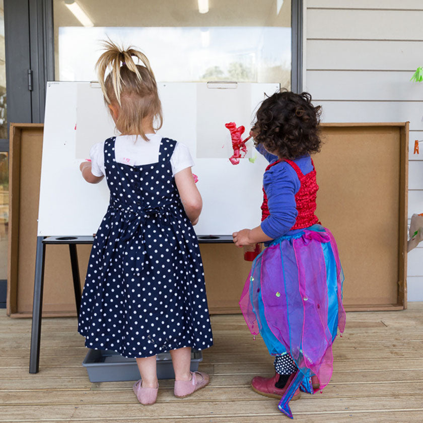 Two little girls painting on an easel at Spotted Frog Preschool