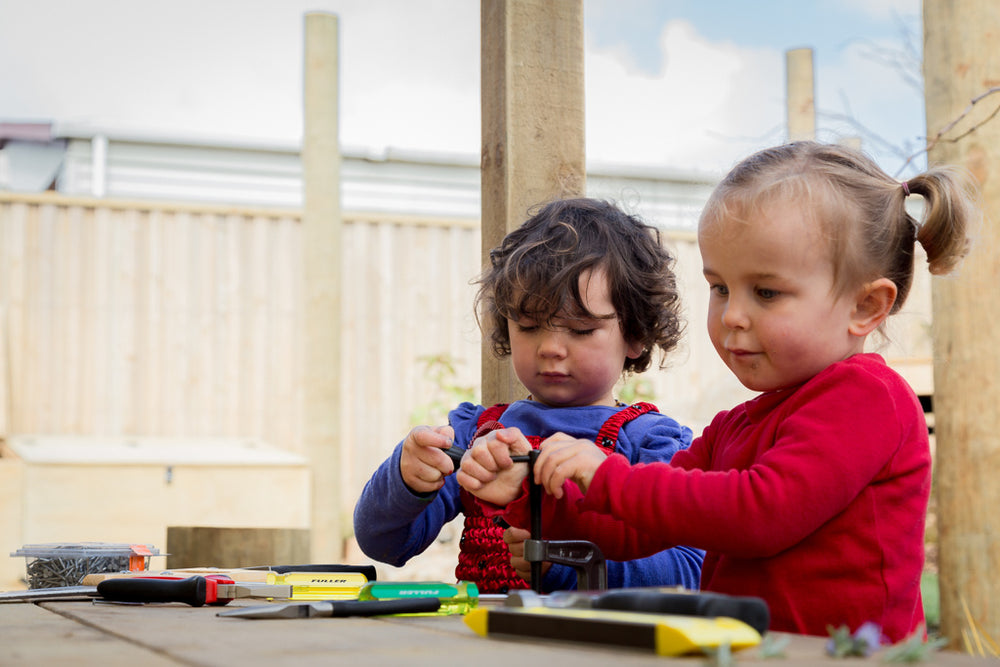 Two girls playing with tools on a workbench at Spotted Frog Preschool