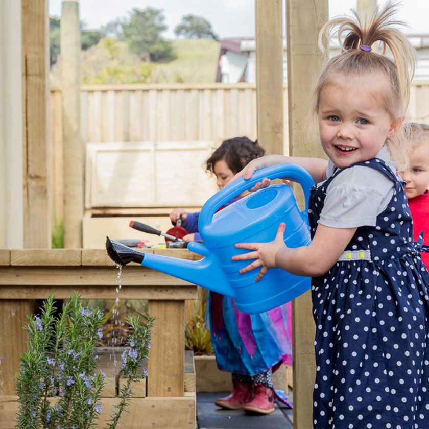 A preschool girl watering plants with a blue watering can at Spotted Frog Preschool
