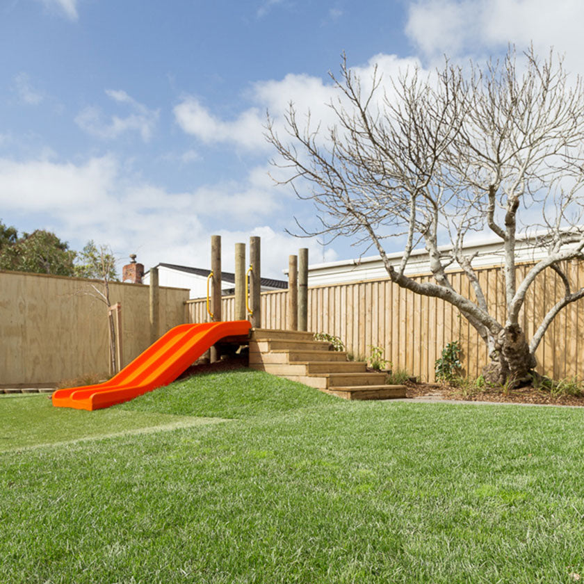 Outdoor shot of an orange slide and green lawn at Spotted Frog Preschool