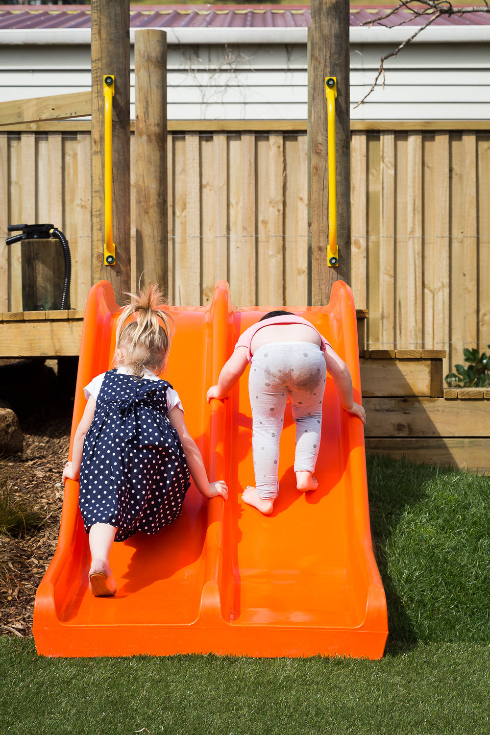 Two girls playing on an orange slide at Spotted Frog Preschool