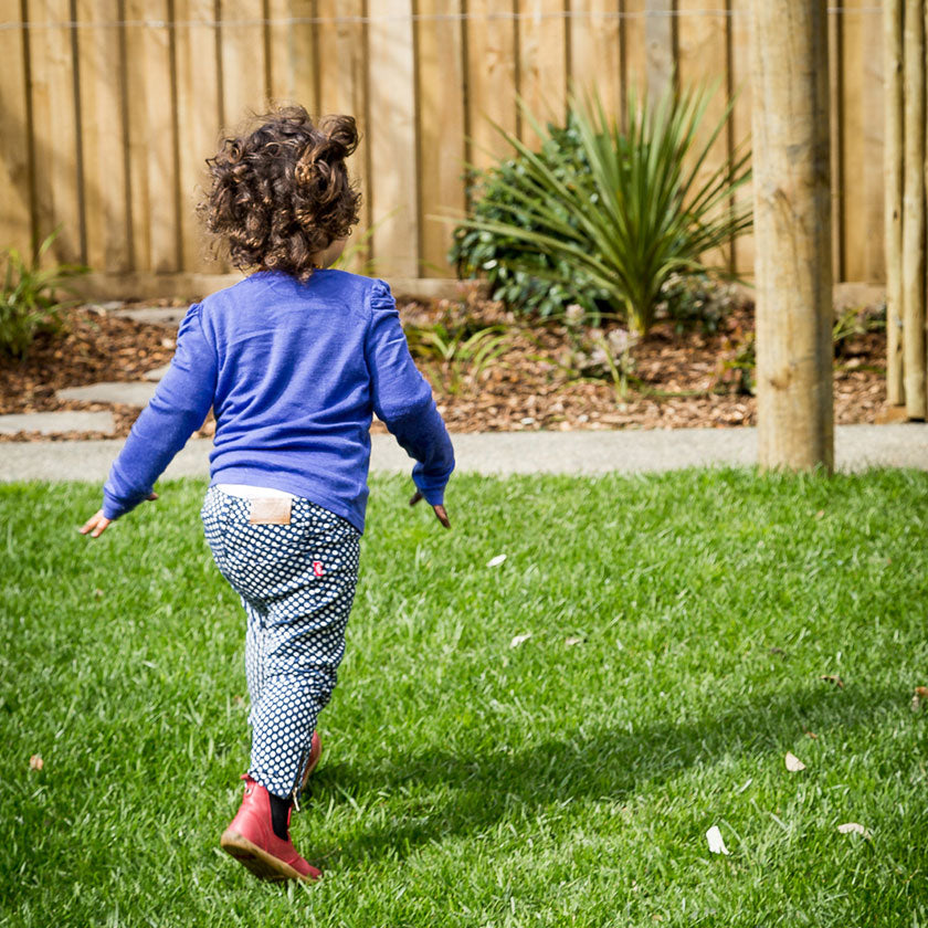 A preschooler running on green grass at Spotted Frog Preschool