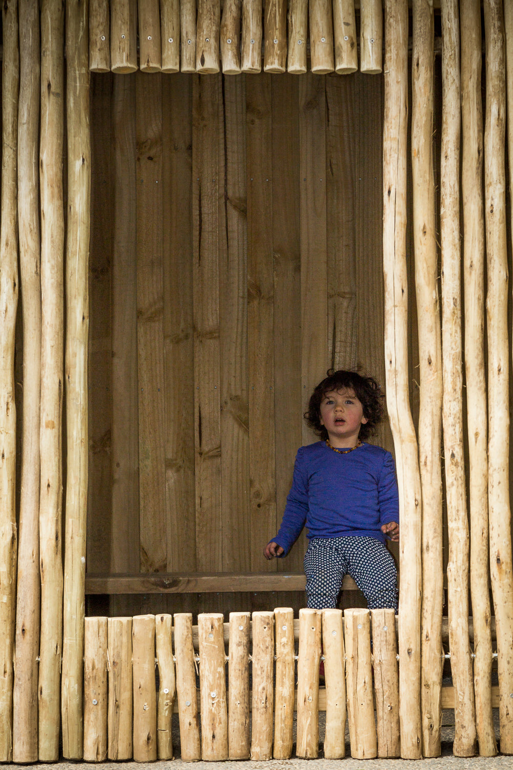 A small girl sitting in a wooden hut at Spotted Frog Preschool