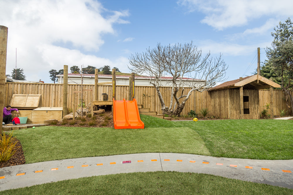 Orange slide, wooden hut, bike track and grass at Spotted Frog Preschool