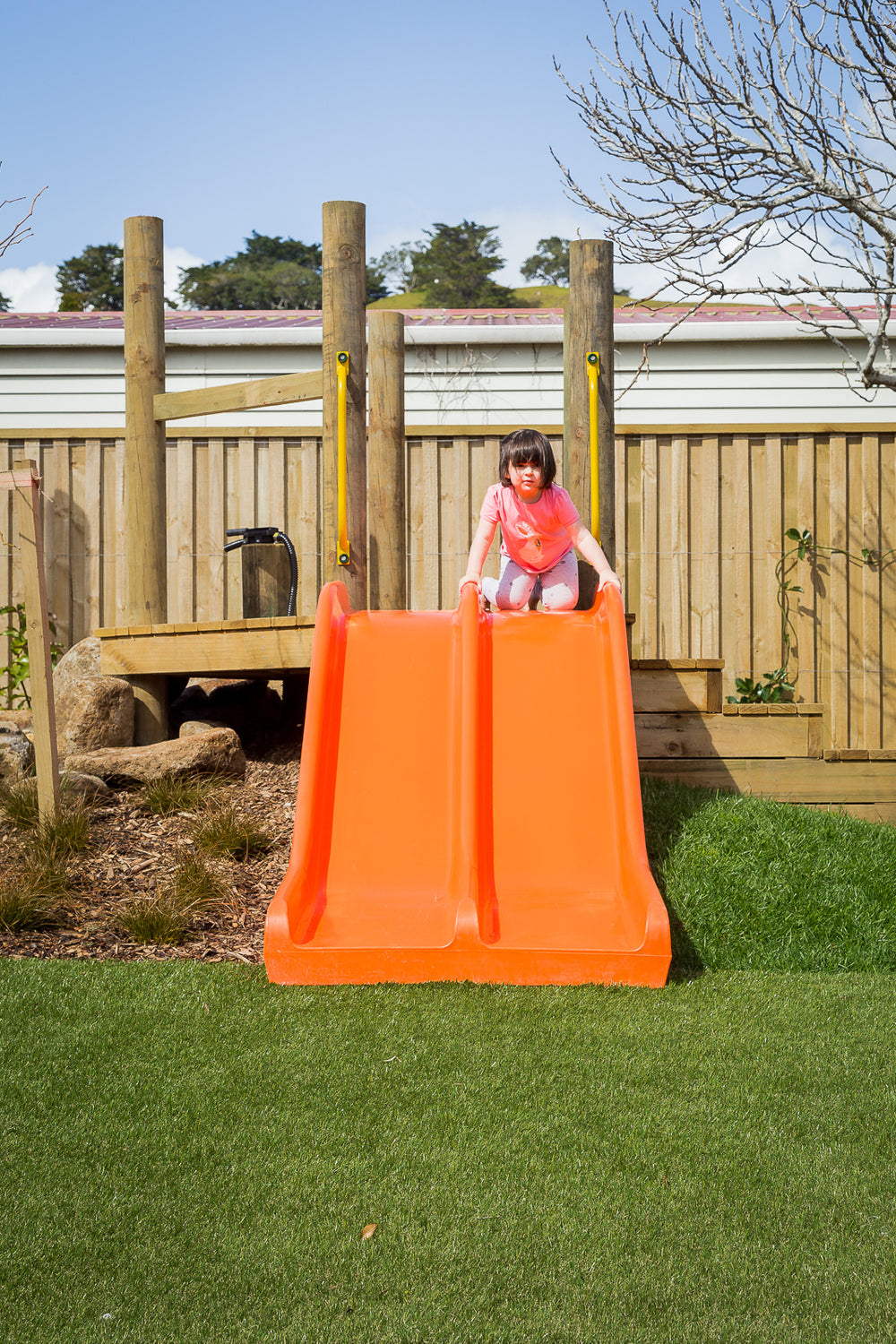A young preschool girl playing on an orange slide at Spotted Frog Preschool