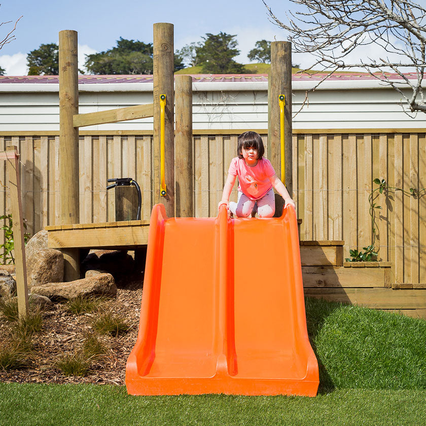 A little girl on an orange slide at Spotted Frog Preschool
