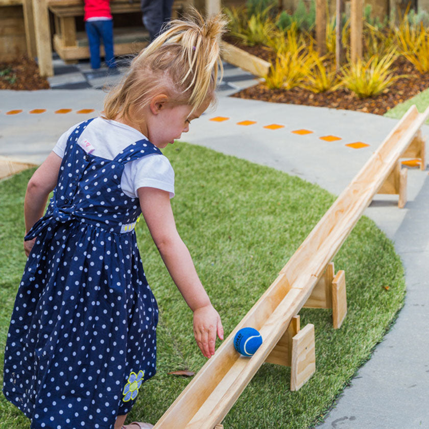 A preschooler pushing a blue tennis ball at Spotted Frog Preschool
