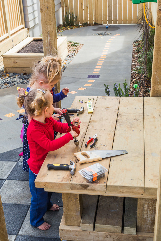 Two preschool girls playing with tools on a workbench at Spotted Frog Preschool