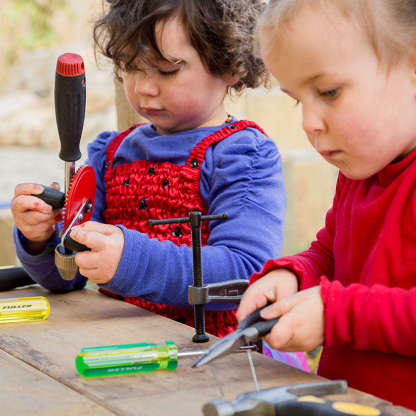 Two preschool girls playing with tools at a workbench at Spotted Frog Preschool