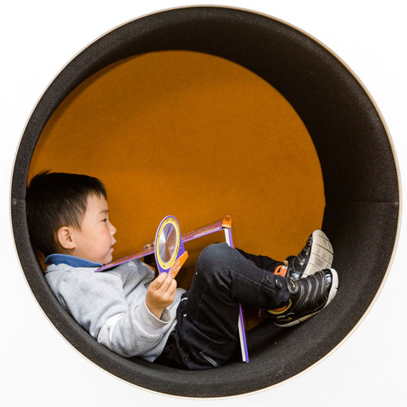 A preschool boy playing with toys in a circle tunnel at Spotted Frog Preschool