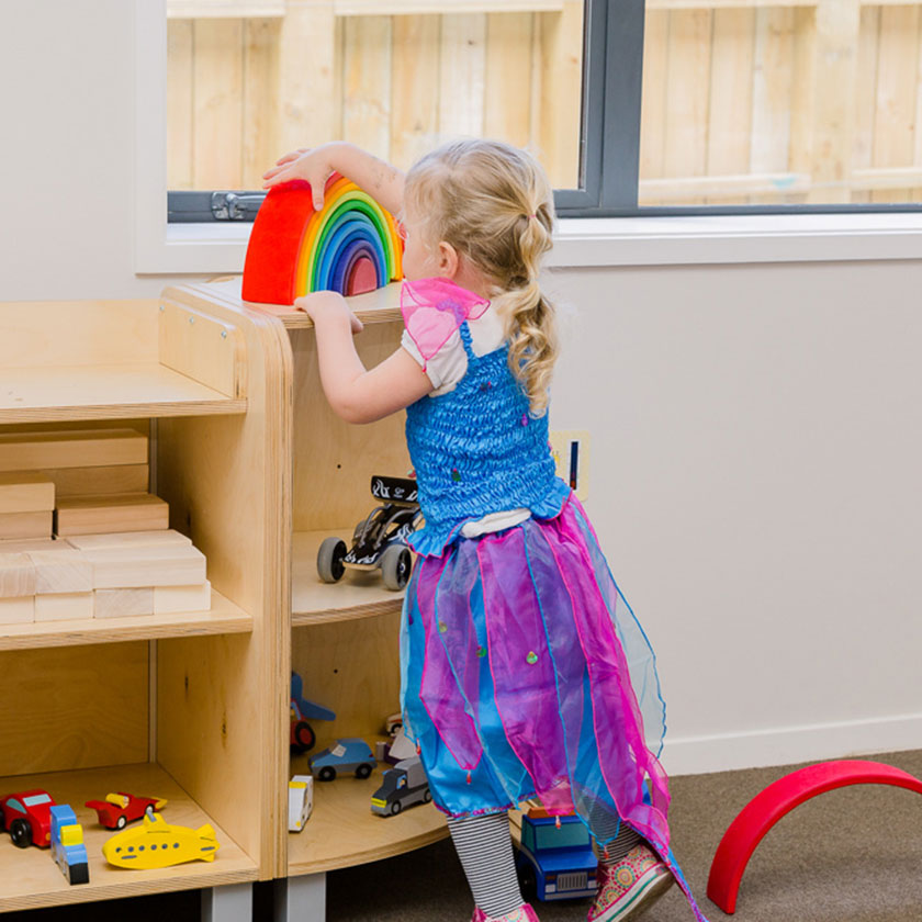 A preschool girl playing with a wooden rainbow at Spotted Frog Preschool