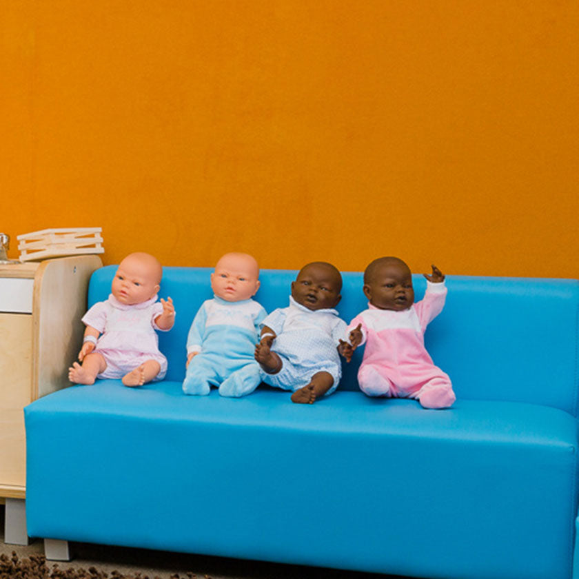 Baby dolls sitting on a blue couch at Spotted Frog Preschool