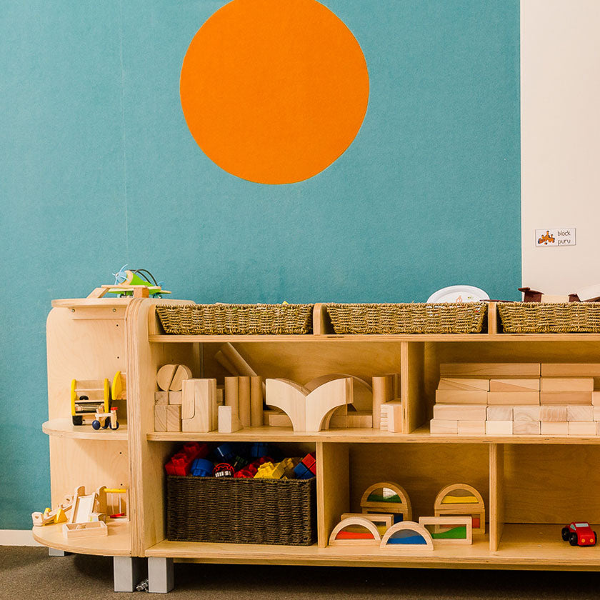 Wooden toy table against a blue wall with an orange spot at Spotted Frog Preschool