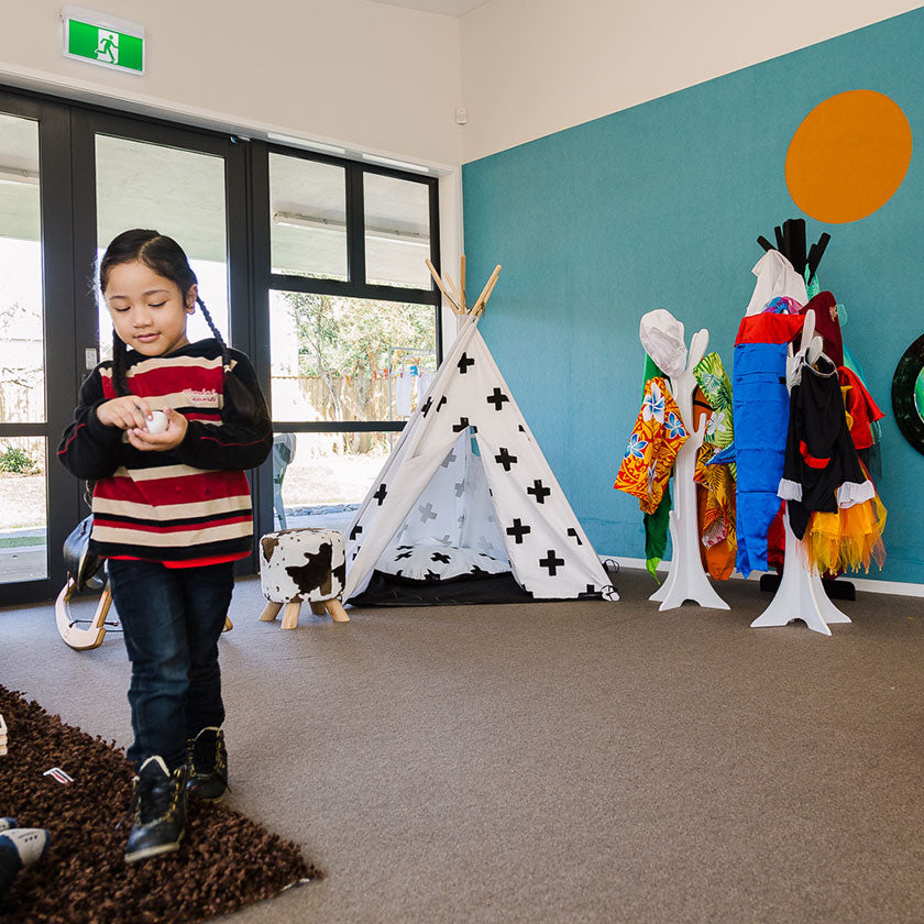 A preschooler playing in front of a teepee