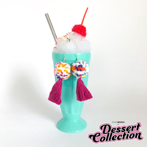 Pom pom earrings made of white, blue, pink, yellow, and green pom poms with purple tassels, displayed hanging from a green milkshake cup in front on a white background.